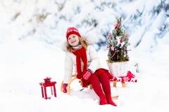 Niños con el árbol de navidad Diversión del invierno de la nieve para los niños Imagenes de archivo
