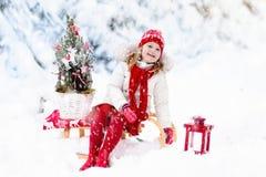 Niños con el árbol de navidad Diversión del invierno de la nieve para los niños Fotografía de archivo libre de regalías