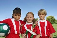 Niños con el balón de fútbol y el trofeo imagen de archivo