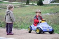 Niños con el coche del juguete al aire libre fotos de archivo