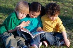 Niños con el libro en una hierba en parque Fotos de archivo libres de regalías