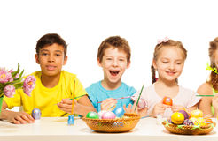 Niños con el muchacho de risa que colorea los huevos del este Foto de archivo libre de regalías