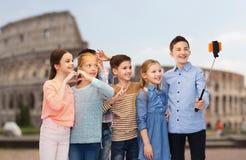 Niños con el palillo del selfie del smartphone sobre coliseo Foto de archivo