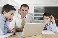 Niños con el papá en la computadora portátil Imagen de archivo libre de regalías