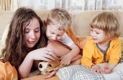 Niños con el perrito del beagle en la cama Fotografía de archivo