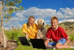 Niños con el perro y las computadoras portátiles Imagenes de archivo