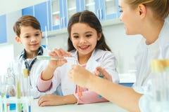 Niños con el profesor en el laboratorio de la escuela que hace el experimento imagenes de archivo