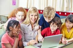 Niños con el profesor en ordenador Fotos de archivo