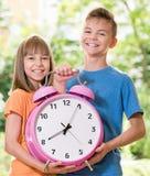 Niños con el reloj grande Imagenes de archivo
