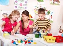 Niños con el sitio del juego de la pintura del profesor. Fotos de archivo
