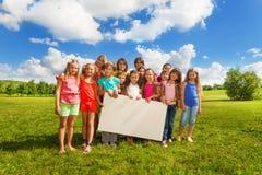 Niños con el tablero para el espacio de la copia Imagen de archivo libre de regalías