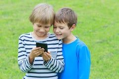 Niños con el teléfono móvil al aire libre Dos muchachos que sonríen, mirando a la pantalla, jugando a juegos o usando el uso tecn Imágenes de archivo libres de regalías