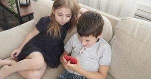 Niños con el teléfono móvil en el sofá metrajes