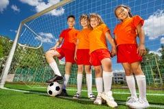 Niños con fútbol en fila cerca de la artesanía en madera foto de archivo
