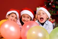 Niños con impulsos por el árbol de navidad Foto de archivo