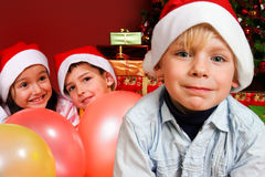 Niños con impulsos por el árbol de navidad Imagenes de archivo