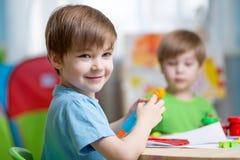 Niños con la arcilla del juego en casa Fotos de archivo