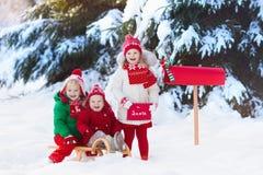 Niños con la letra a Papá Noel en el buzón de la Navidad en nieve Fotografía de archivo