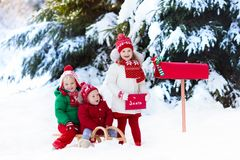 Niños con la letra a Papá Noel en el buzón de la Navidad en nieve Foto de archivo libre de regalías