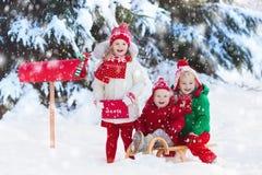 Niños con la letra a Papá Noel en el buzón de la Navidad en nieve Imagen de archivo libre de regalías