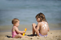 Niños con la loción del bronceado en la playa Imagen de archivo libre de regalías