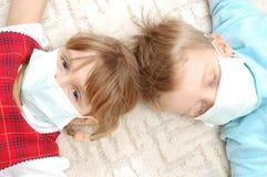 Niños con la máscara de la gripe del pretection fotos de archivo libres de regalías