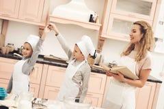 Niños con la madre en cocina Brother y la hermana están bailando, madre está sosteniendo el libro de cocina Foto de archivo libre de regalías