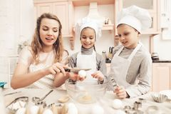 Niños con la madre en cocina La madre es enseñando niños a cómo romper los huevos Fotografía de archivo