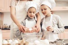 Niños con la madre en cocina La madre es enseñando niños a cómo romper los huevos Fotos de archivo