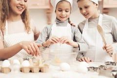 Niños con la madre en cocina La madre es enseñando niños a cómo romper los huevos Fotos de archivo libres de regalías