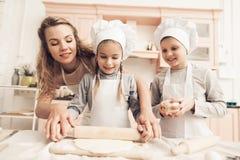 Niños con la madre en cocina La madre está ayudando a niños a desarrollar la pasta Imagenes de archivo