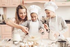 Niños con la madre en cocina La madre está ayudando a la mezcla de la agitación de los niños en cuenco Fotografía de archivo