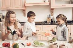 Niños con la madre en cocina La madre está ayudando a niños prepara las verduras para la ensalada Imagenes de archivo