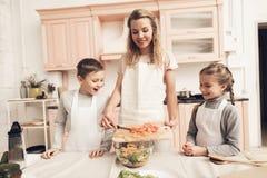 Niños con la madre en cocina La madre está haciendo la ensalada y los niños están mirando Foto de archivo libre de regalías