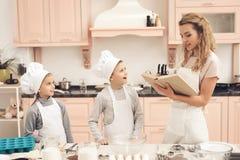 Niños con la madre en cocina La madre está leyendo el libro de cocina Fotos de archivo