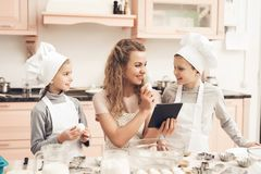 Niños con la madre en cocina La familia está leyendo receta en la tableta Fotografía de archivo