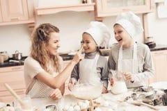 Niños con la madre en cocina La familia está manchando juguetónamente la pasta en nariz Fotos de archivo