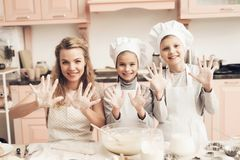 Niños con la madre en cocina La familia está mostrando en las manos de la cámara en harina Foto de archivo libre de regalías