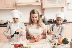Niños con la madre en cocina La familia está preparando las verduras para la ensalada Fotos de archivo