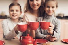 Niños con la madre en cocina La familia está sosteniendo las tazas con té Imagen de archivo libre de regalías