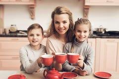 Niños con la madre en cocina La familia está sosteniendo las tazas con té Imágenes de archivo libres de regalías