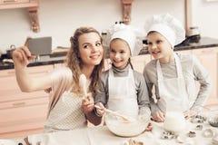 Niños con la madre en cocina La familia está tomando el selfie en el teléfono Fotografía de archivo