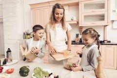Niños con la madre en cocina Los niños están ayudando a la madre a hacer la ensalada Fotografía de archivo