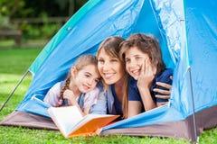 Niños con la madre que celebra el libro en tienda Foto de archivo