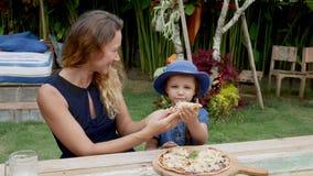Niños con la madre que come la pizza en la playa almacen de metraje de vídeo