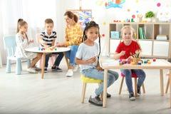 Niños con la maestra en la lección de pintura imagenes de archivo
