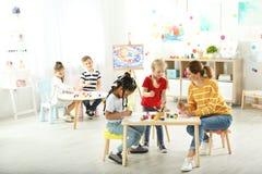 Niños con la maestra en la lección de pintura imagen de archivo libre de regalías
