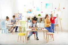 Niños con la maestra en la lección de pintura imagen de archivo