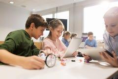 Niños con la PC de la tableta que programa en la escuela de la robótica Fotografía de archivo libre de regalías
