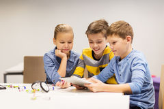 Niños con la PC de la tableta que programa en la escuela de la robótica Foto de archivo